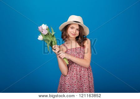 Happy charming little girl standing and holding bouquet of tulips over blue background