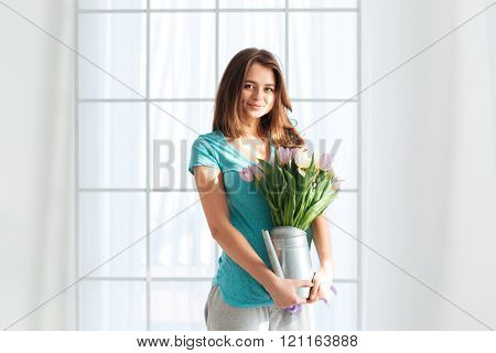 Smiling attractive young woman standing and holding watering can with bouquet of flowers near the window