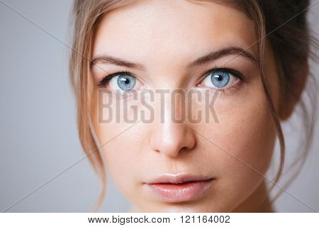 Closeup portrait of a beautiful woman looking at camera over gray background