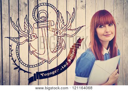 Smiling hipster woman holding document against wooden planks