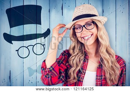 Gorgeous smiling blonde hipster posing against wooden planks