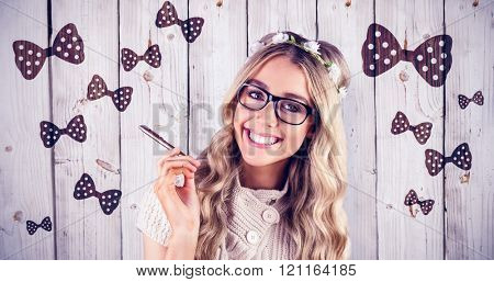 Gorgeous smiling blonde hipster holding pen against wooden background