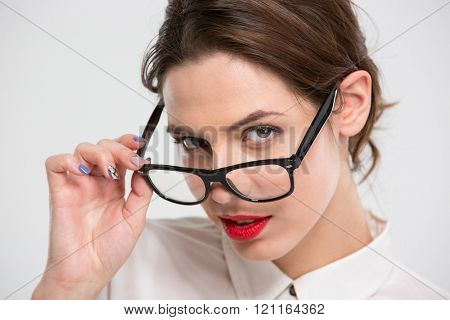Portrait of sensual beautiful young business woman with red lips looking over glasses over white background