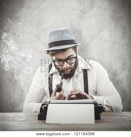 Hipster smoking pipe while working at desk against white and grey background