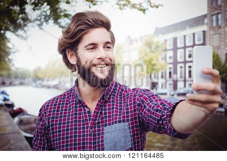 Happy hipster taking selfie against canal in amsterdam