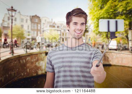 Happy man taking selfie against bridge in amsterdam