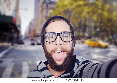 Portrait of happy hipster sticking out tongue against blurry new york street