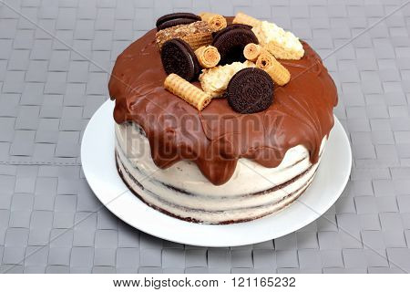 Cake glazed with milk chocolate and decorated with waffles and cookies on white plate