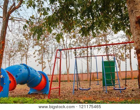 The colorful swing set and the big tube toy in the garden.