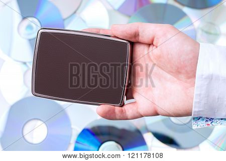 Man's hand with portable disk over CD's background.