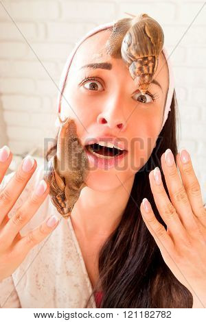 portrait of young afraid darkhaired woman with snails achatina giant on her face poster