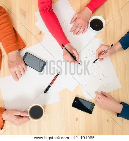 Top view of businesspeople hands holding pens papers smartphones and coffee on the table. Teamwork concept. Business team discussing talking in cafe.