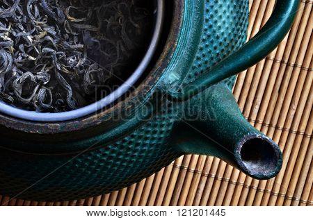 Oriental tea pot with dry tea inside. Still life.