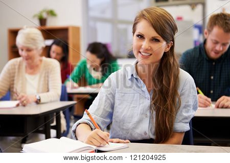 Young woman at an adult education class looking to camera