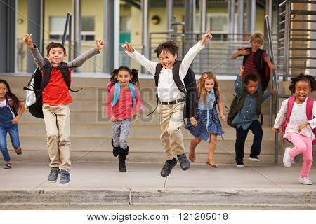 A group of energetic elementary school kids leaving school