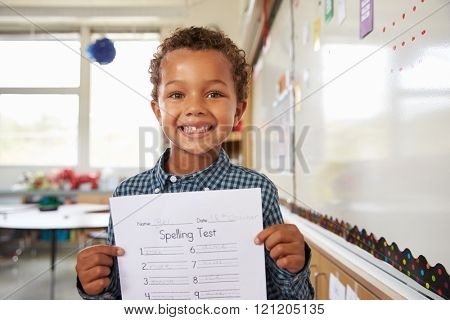 Portrait of elementary school boy holding up his test paper