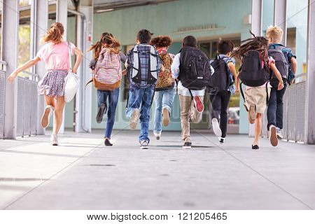Group of elementary school kids running at school, back view
