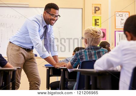 Smiling teacher leaning on elementary school pupilâ??s desk