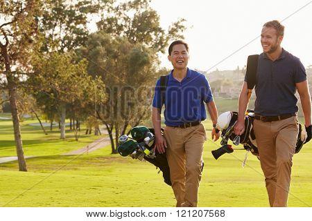 Two Male Golfers Walking Along Fairway Carrying Bags