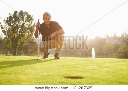 Male Golfer Lining Up Putt On Green