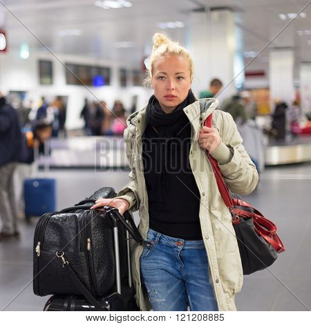 Female traveler transporting luggage in airport.