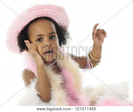 Close-up image of an adorable 2 year old diva in beads, boas and bangles.  She's looking at the viewer with one hand on her cheek.  On a white background.