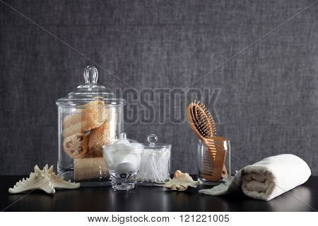 Bathroom set with wooden comb, towel and wisps on grey background