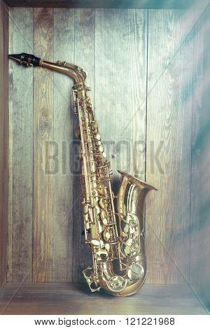 Golden saxophone on wooden background