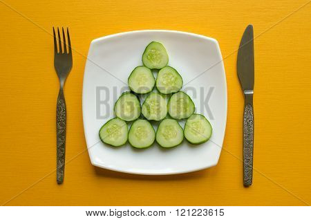 Plate with sliced cucumber, fork and knife