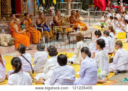 NAKHON PATHOM, THAILAND, JANUARY 16, 2016 : Buddhist monks and women are chanting and praying outside the Wat Samphran temple in Nakhon Pathom near Bangkok, Thailand