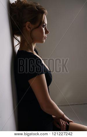 Profile of pretty brunette dressed in black dress