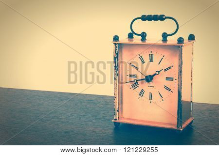 Retro styled image of vintage square table clock on a wooden table.