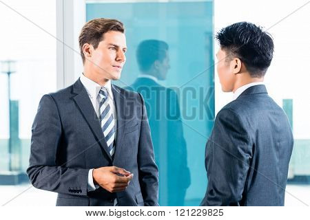 Asian and Caucasian business men discussing in front of city skyline