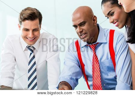 Business team with Indian CEO in meeting