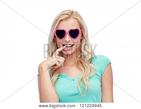 emotions, expressions, summer and people concept - smiling young woman or teenage girl in heart shape sunglasses