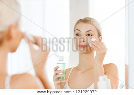 beauty, skin care and people concept - smiling young woman applying lotion to cotton disc for washing her face at bathroom