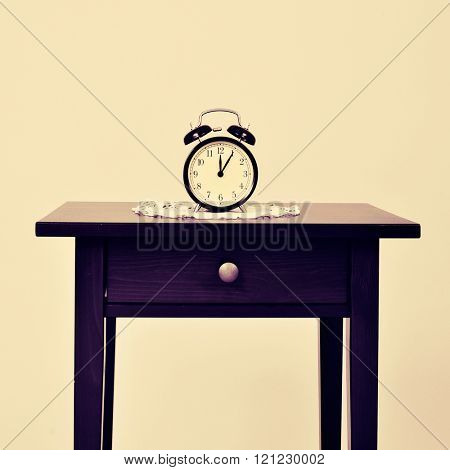a black alarm clock placed on a crochet doily, on a black table, with a retro effect