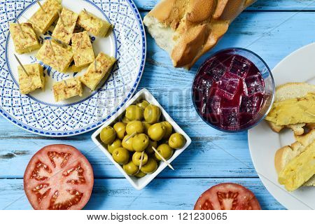 high-angle shot of a plate with tortilla de patatas, spanish omelet, served as tapas, a glass with tinto de verano, bread and a bowl with olives on a colorful blue wooden table