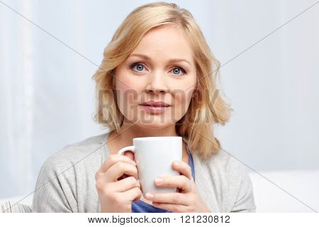 people, drinks and leisure concept - woman with cup of tea or coffee at home