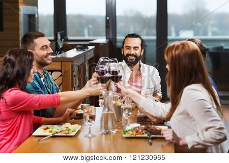 leisure, celebration, food and drinks, people and holidays concept - smiling friends having dinner and drinking red wine at restaurant