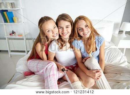 friendship, people, pajama party and technology concept - happy friends or teenage girls with monopod taking selfie at home