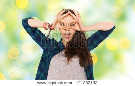 people and teens concept - happy smiling pretty teenage girl making face and having fun over green summer holidays lights background