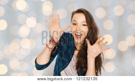 people and teens concept - happy laughing pretty teenage girl showing hands over holidays lights background