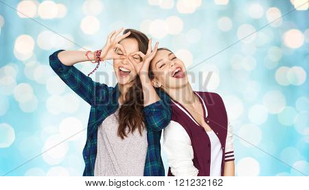 people, friends, teens and friendship concept - happy smiling pretty teenage girls having fun and making faces over blue holidays lights background