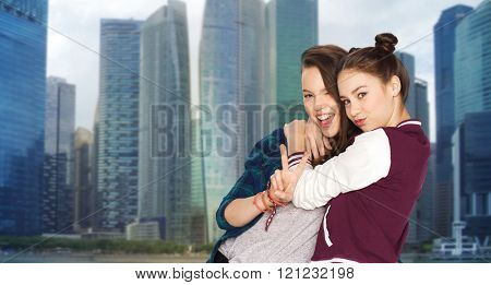 people, teens, friendship, travel and tourism concept - happy smiling pretty teenage girls hugging and showing peace hand sign over singapore city background