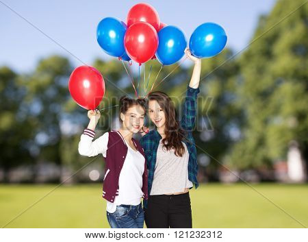 people, friends, teens, holidays and party concept - happy smiling pretty teenage girls with helium balloons over summer park background