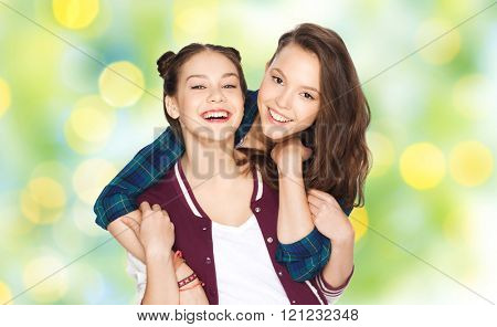 people, friends, teens and friendship concept - happy smiling pretty teenage girls hugging over green summer holidays lights background