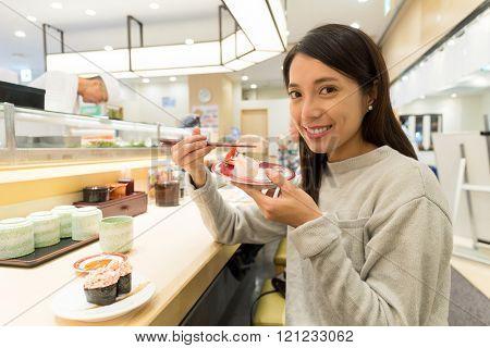 Woman having sushi at japanese restaurant