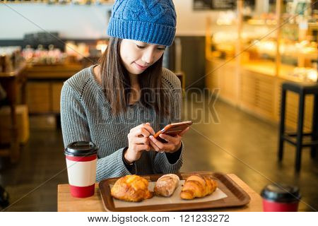 Woman use of cellphone in cafe at morning