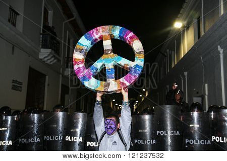 Quito, Ecuador - August 27, 2015: Man wearing facial paint holding large peace symbol in front of li